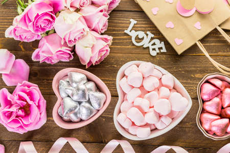 Pink roses with chocolates on rustic wood table.