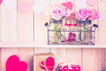 Pink roses in jars and gifts on rustic wood shelf for Valentines DAy.