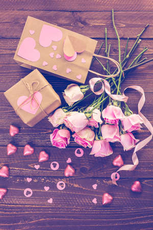mode made: Pink roses and gift wrapped in recycled paper on rustic wood table.