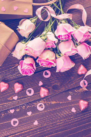 nad made: Pink roses and gift wrapped in recycled paper on rustic wood table.