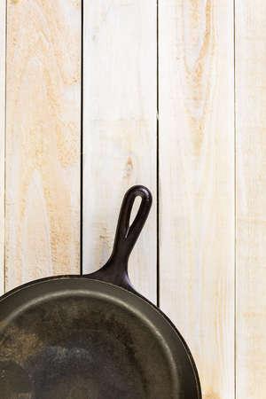 Cast iron skillet on rustic wood table.