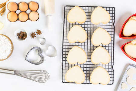 wire pin: Baking heart shaped sugar cookies for Valentines Day. Stock Photo