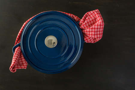 dutch: Enameled blue cast iron covered dutch oven on black wood table.