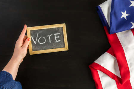 goverment: Vote sign on chalk board next to the American Flag.