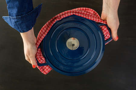 enameled: Enameled blue cast iron covered dutch oven on black wood table.