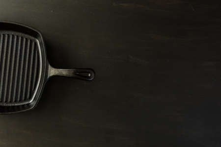 Traditional cast iron skillet on black wood table. Banco de Imagens