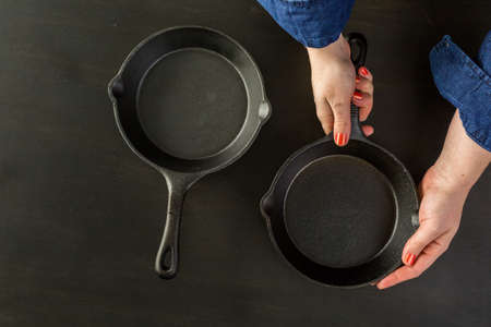skillet: Traditional cast iron skillet on black wood table. Stock Photo