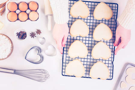 baked treat: Baking heart shaped sugar cookies for Valentines Day. Stock Photo