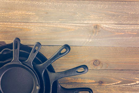 homely: Cast iron skillet on rustic wood table.