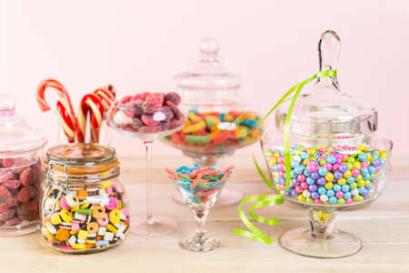 Multicolored candies in glass candy jars. Imagens