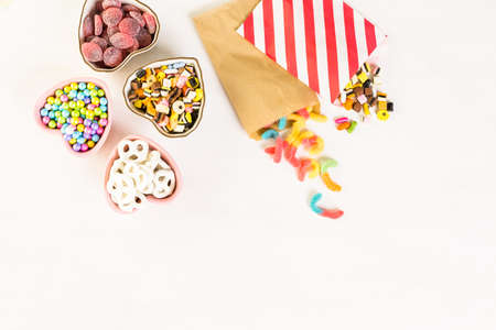 Multicolored candies on a white table. Imagens
