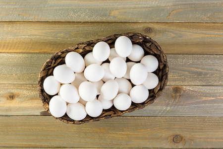 Farm fresh eggs in wicker basket on the table.