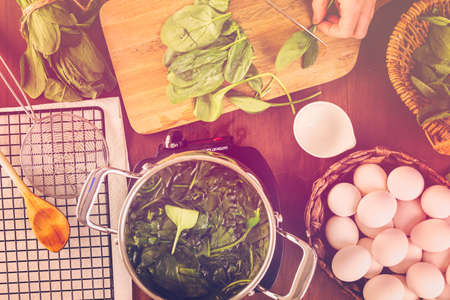 Dyeing Easter eggs with natural dye from spinach. Stock Photo