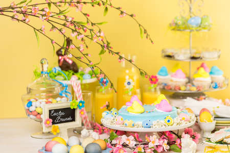 baked treat: Dessert table with Easter cake decorated with traditional Easter marshmallow chicks.