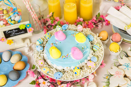 Dessert table with Easter cake decorated with traditional Easter marshmallow chicks.