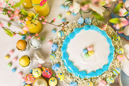 Dessert table set with cake and cupcakes for Easter brunch.