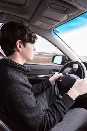 Teenage boy learning to drive on interstate highway.