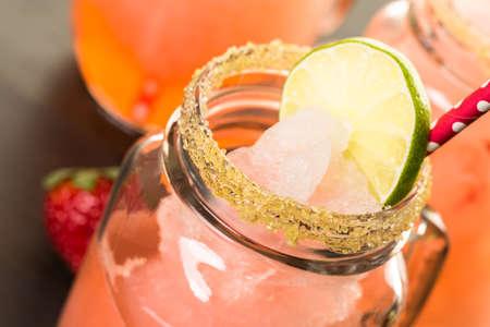 Frozen strawberry margarita cocktail in drinking mason jar.
