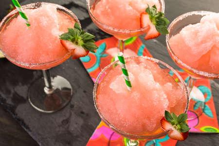 Frozen strawberry margarita cocktail in margarita glass.