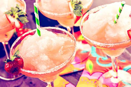 frozen food: Frozen strawberry margarita cocktail in margarita glass.