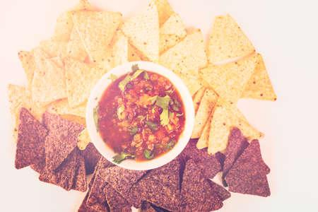 tortilla de maiz: salsa fresca en un tazón blanco con chips de tortilla de maíz blanco y azul.