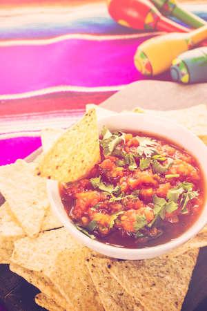 tortilla de maiz: salsa fresca en un recipiente blanco con chips de tortilla de ma�z blanco.