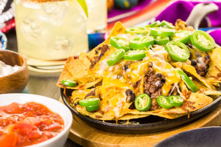 Claasic nachos with ground beef and fresh jalapeno chile peppers.
