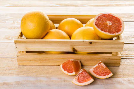 wood crate: Fresh ryby red grapefruits in wood crate. Stock Photo