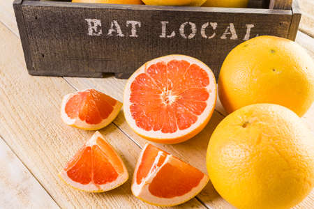 grapefruits: Fresh ryby red grapefruits in wood crate. Stock Photo