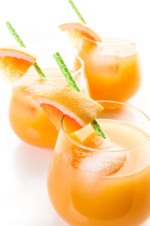Organic ryby red grapefruit juice in small glass with ice. Stock Photo