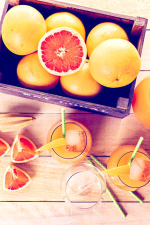 ruby red: Organic ruby red grapefruit juice in small glass with ice.