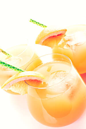 ruby red: Organic ruby red grapefruit juice in small glasses with ice.
