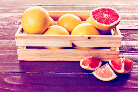 Fresh ruby red grapefruits in wood crate.