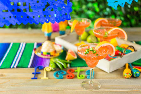 piperaceae: Spicy grapefruit margarita on ice in margarita glasses on the table in the garden. Stock Photo