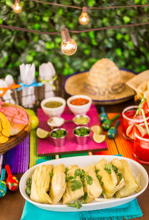 Party table with tamales, strawberry margartisa and pan dulche bread.