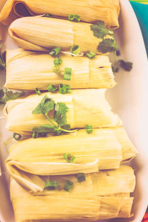 Home made tamales on serving plate on the party table. Stock Photo