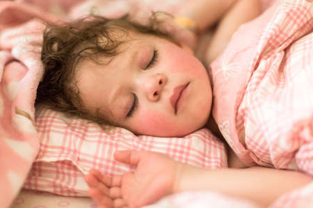 Cute toddler sleeping in her bed with pink bedding. 版權商用圖片 - 57299532