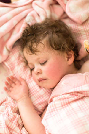 matress: Cute toddler sleeping in her bed with pink bedding.