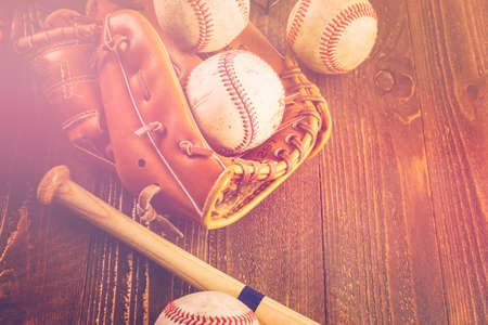 Baseball ball and glove on a wood board.
