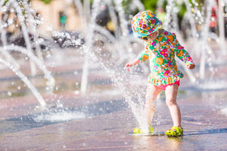 Niño que juega con pequeñas fuentes de la plaza urbana.