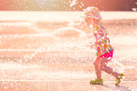 urban redevelopment: Toddler playing with small fountains on the urban plaza.