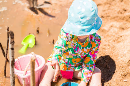 Toddler playing with sand toys on the beach. Stock Photo