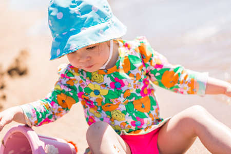sand toys: Toddler playing with sand toys on the beach. Stock Photo