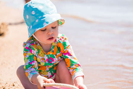 chatfield: Toddler playing with sand toys on the beach. Stock Photo