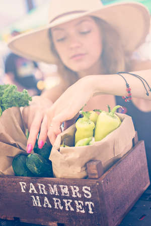 Young woman shopping at the local Farmers market.