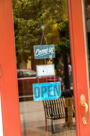come in: Open and come in signs on the door of the store.