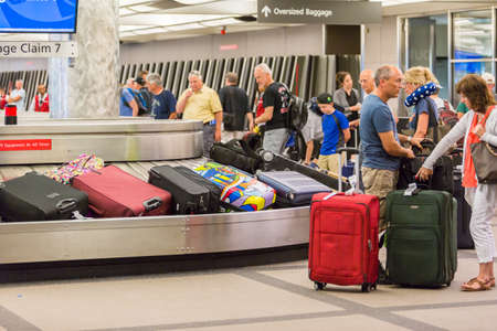 Denver, Colorado, USA-June 22, 2016.  Travelers waiting for their luggage at the baggage carousel. 新闻类图片