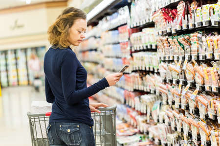 bring: Young woman shopping in the lunch meat section at the grocery store.