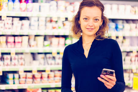 bring: Young woman shopping in the yogurt section at the grocery store.