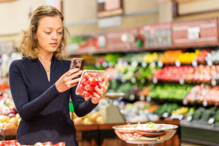 food technology: Young woman shopping in the fresh produce section at the grocery store. Stock Photo